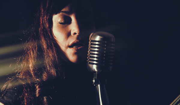female vocalist in the recording studio, singing with eyes shut