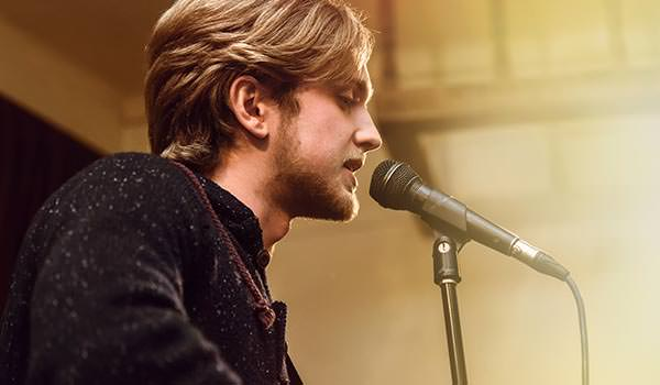 singer songwriter performing on stage