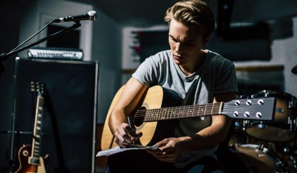 Singer in the studio writing lyrics with guitar