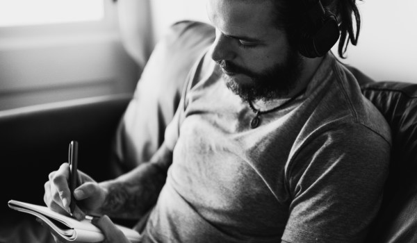 Male singer songwriter penning lyrics with headphones on